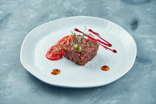 De verse tartaar van het biefstukrundvlees met kappertjes, kruiden, uien op een witte plaat. detailopname.