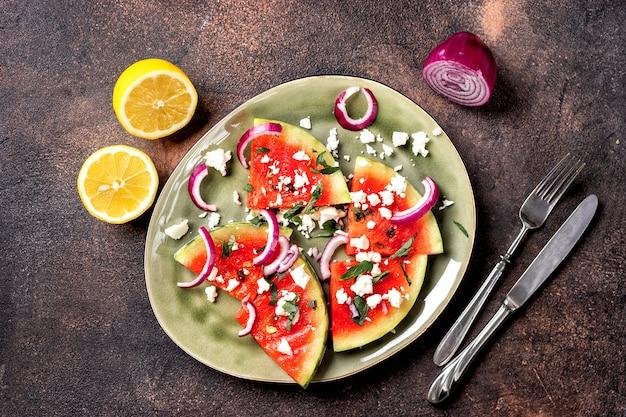 De verse zomer roosterde watermeloenplakken met feta-kaas, munt, uien op bruine achtergrond