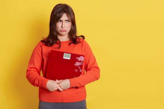 De verstoorde jonge volwassen dame kleedt vrijetijdskleding die vloerweegschaal in handen houdt, wegkijkend met steenbolklippen, verdriet uitdrukt, geïsoleerd over gele muur.