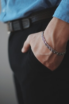 De verticale close-up die van een mannetje is ontsproten dat een zilveren armband met van hem draagt dient de zakken in