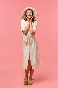De verticale dwaze en kokette mooie kaukasische vrouw van gemiddelde lengte in kleding en hoed, die zonnescherm toepassen alvorens naar strand te gaan, genietend van zomervakantie, die zich vrij over roze bevindt