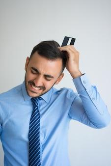 De verwarde jonge creditcard van de bedrijfsmensenholding