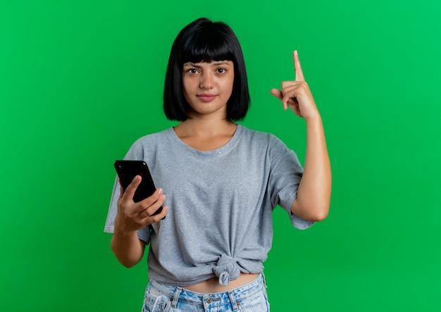 De verwarde jonge donkerbruine kaukasische vrouw houdt telefoon en wijst omhoog geïsoleerd op groene achtergrond met exemplaarruimte
