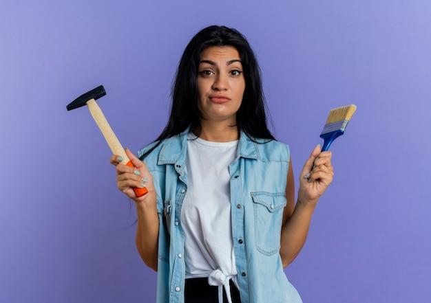 De verwarde jonge kaukasische vrouw houdt hamer en verfborstel die op purpere achtergrond met exemplaarruimte wordt geïsoleerd
