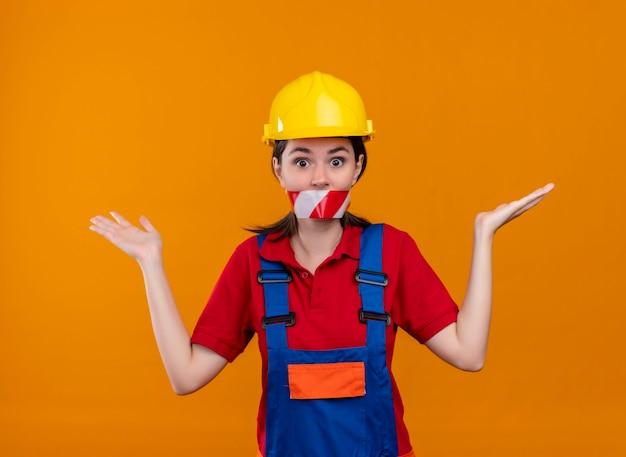De verwarde jonge mond van het bouwersmeisje verzegeld met waarschuwingstape houdt handen omhoog op geïsoleerde oranje achtergrond
