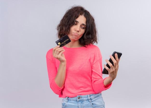 De verwarde jonge mooie kaart van de vrouwenholding en mobiele telefoon op geïsoleerde witte muur met exemplaarruimte