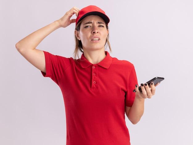 De verwarde jonge mooie leveringsvrouw in uniform houdt telefoon vast en legt hand op hoofd dat op witte muur wordt geïsoleerd
