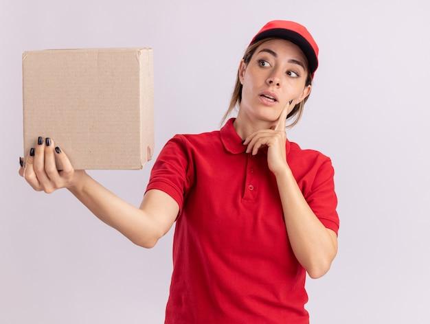 De verwarde jonge mooie leveringsvrouw in uniform legt de hand op het gezicht en kijkt naar kartonnen doos geïsoleerd op een witte muur