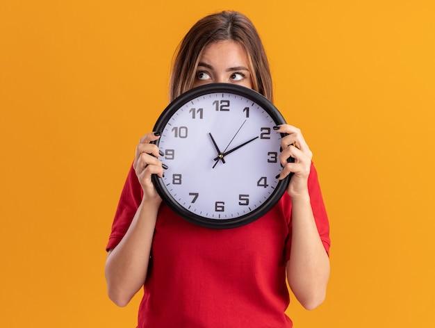De verwarde jonge mooie vrouw houdt klok die kant bekijkt die op oranje muur wordt geïsoleerd