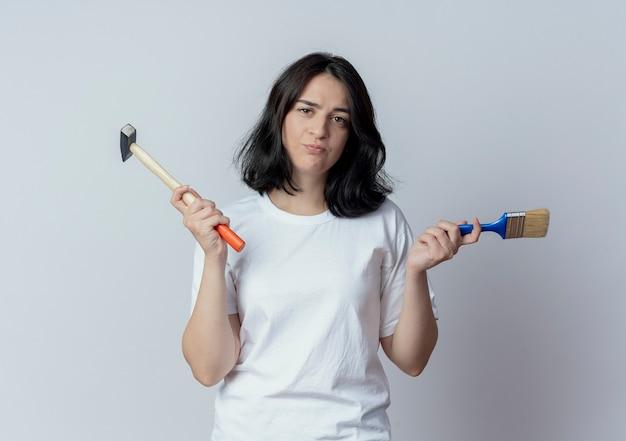 De verwarde jonge vrij kaukasische hamer en de verfborstel van de meisjesholding die op witte achtergrond wordt geïsoleerd