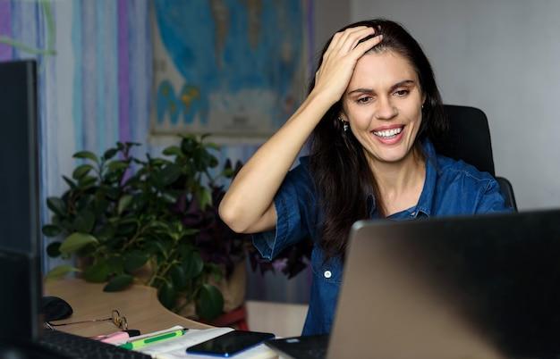 De verwarde jonge vrouw werkt online met laptop