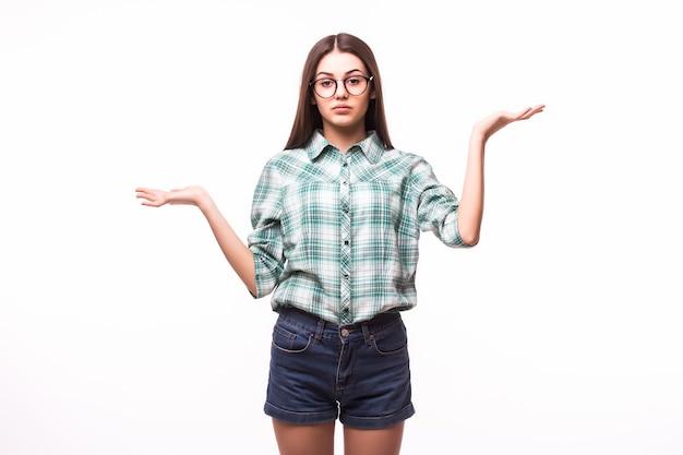 De verwarde jonge zakenvrouw haalt haar schouders op met een onnozel gebaar