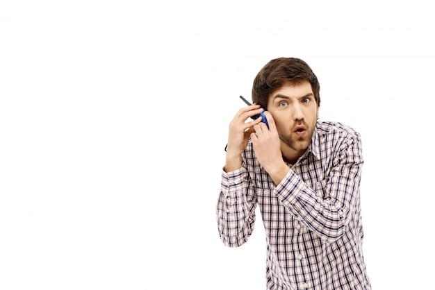 De verwarde mens houdt walkie-talkie dichtbij oor