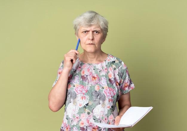De verwarde oudere vrouw houdt notitieboekje en zet pen op gezicht dat op olijfgroene muur wordt geïsoleerd