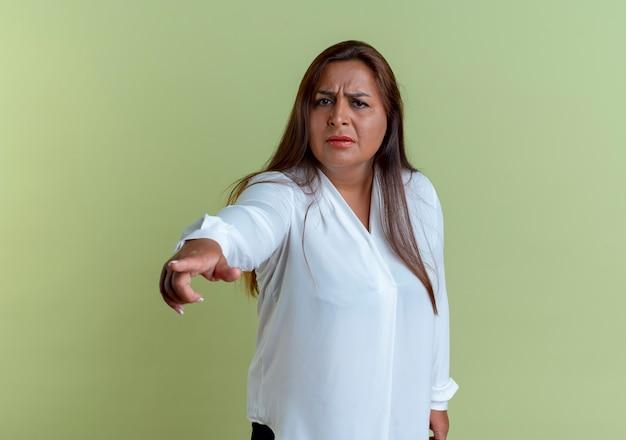 De verwarde toevallige kaukasische vrouw van middelbare leeftijd wijst naar kant