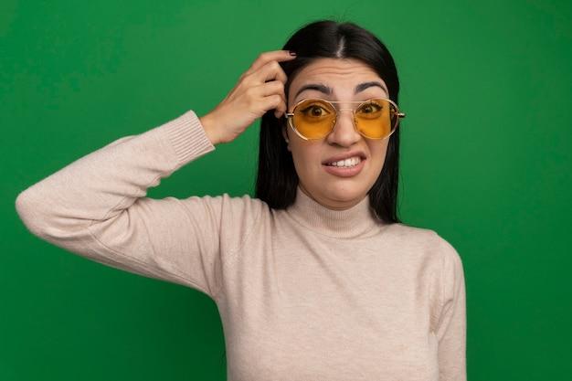 De verwarde vrij donkerbruine vrouw in zonnebril legt vinger op hoofd dat op groene muur wordt geïsoleerd