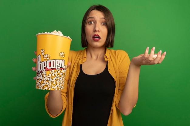 De verwarde vrij kaukasische vrouw houdt geïsoleerde emmer popcorn