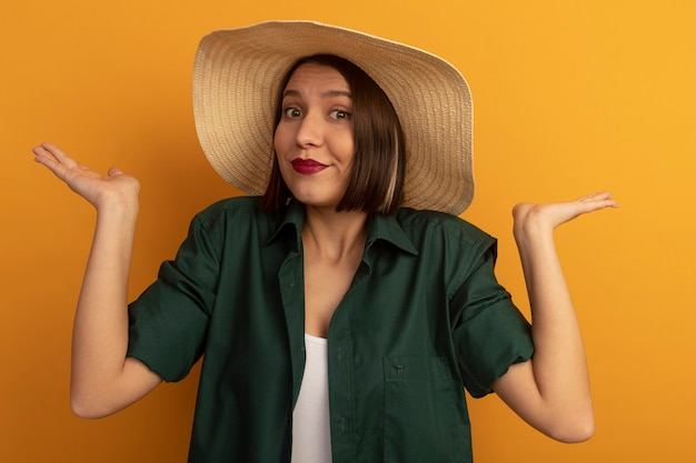 De verwarde vrij kaukasische vrouw met strandhoed houdt handen open op sinaasappel