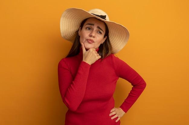 De verwarde vrij kaukasische vrouw met strandhoed houdt kin en bekijkt kant op sinaasappel