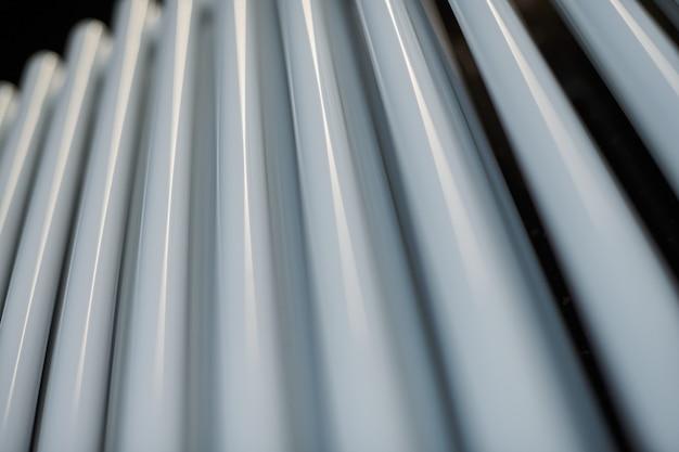 De verwarmende radiator in bureau, sluit omhoog. witte warmtewisselaars. ijzer aluminium stoomradiator. pijp patroon.