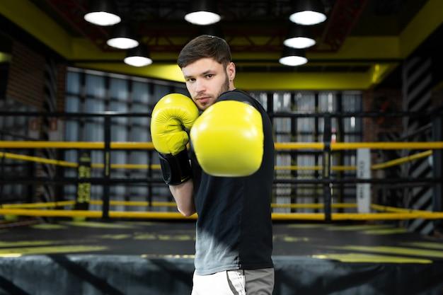 De verzamelde atleet in de boksschool oefent boksstoten tijdens de training en kijkt naar de camera
