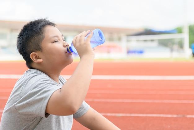 De vette aziatische jongen drinkt water uit een plastic fles