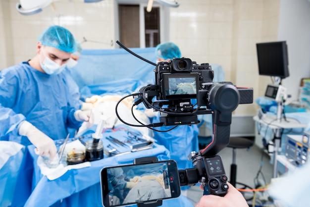 De videograaf fotografeert de chirurg en assistenten in de operatiekamer met chirurgische apparatuur