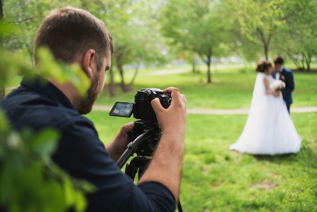 De videograaf schiet de getrouwden in de tuin in de zomer.