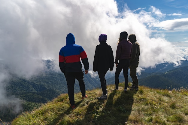 De vier actieve mensen die op de berg staan met een prachtig uitzicht
