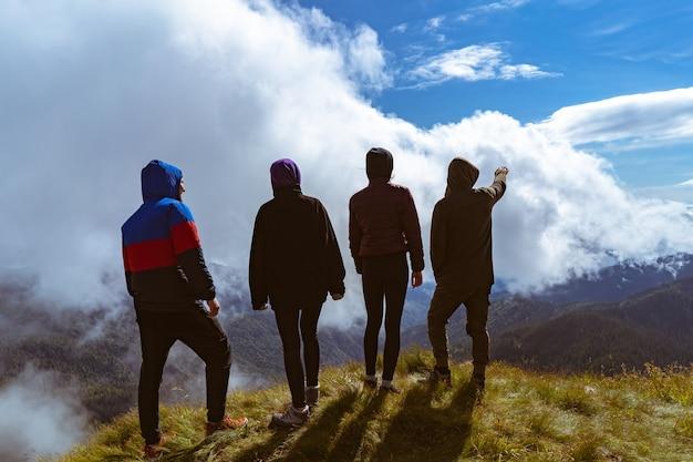 De vier mensen die op de berg staan met een prachtig uitzicht