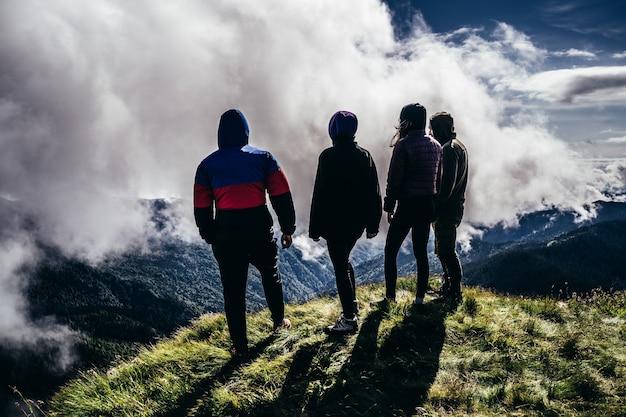 De vier mensen staan op een berg tegen prachtige wolken