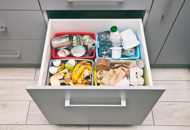 De vier verschillende containers voor het sorteren van afval. voor plastic, papier, metaal en organisch afval