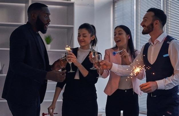 De vier zakenmensen die champagne drinken en sterretjes vasthouden