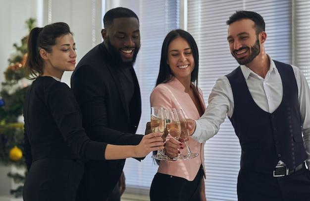 De vier zakenmensen die champagne drinken
