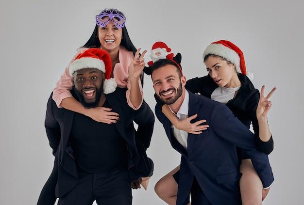De vier zakenmensen die kerstmis vieren en gebaren maken