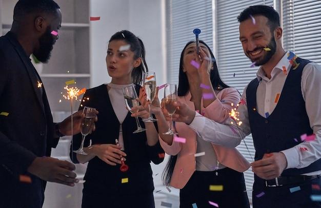 De vier zakenmensen hebben een kantoorfeest met champagne en confetti
