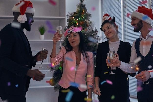 De vier zakenmensen in rode hoed die champagne drinken