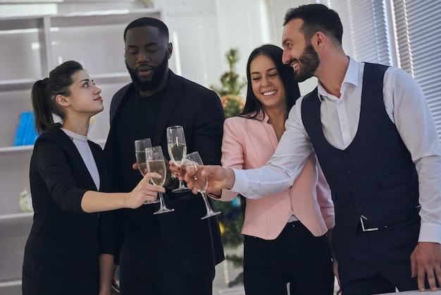 De vier zakenmensen klinken met een bril