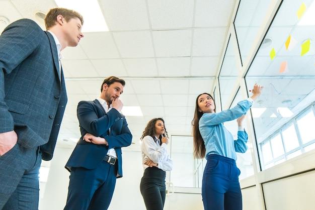 De vier zakenmensen tekenen op het kantoorglas