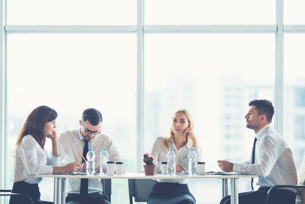 De vier zakenmensen zitten aan de kantoortafel bij het panoramische raam