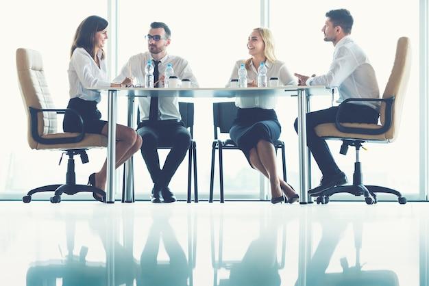 De vier zakenmensen zitten aan de kantoortafel bij het panoramische raam Premium Foto
