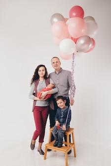 De viering, leuke tijd doorbrengen, familie op het feest. volwassenen en kinderen op een witte achtergrond tussen de gekleurde ballen vieren hun verjaardag