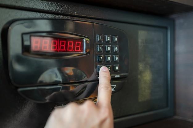De vinger drukt op de cijfertoetsen van de elektrische kluis