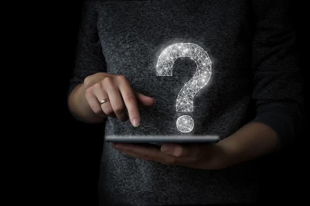 De vinger van de hand drukt op de tablet met een hologram van het vraagteken.