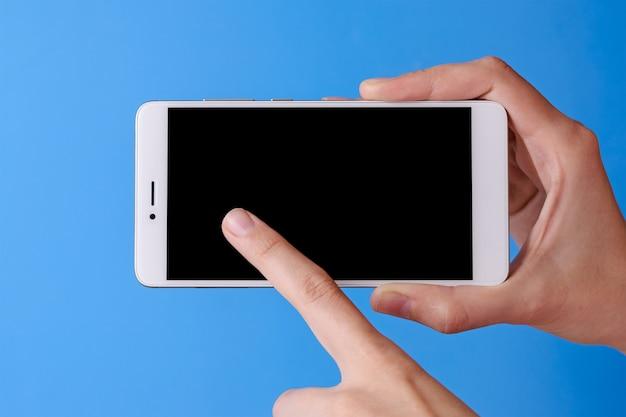 De vinger van de vrouw wat betreft telefoon mobiel met geïsoleerde vertoning op blauwe achtergrond