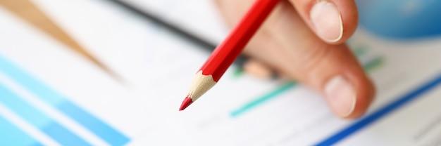 De vingers houden rood potlood op achtergronddiagrammen
