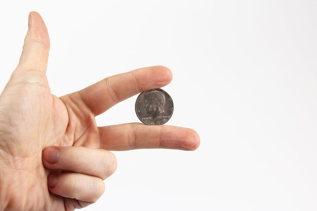 De vingers van de hand die de munt vasthoudt