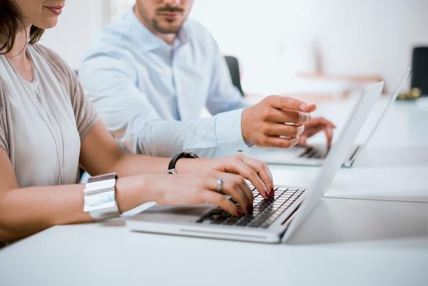 De vingers van een zakenman die aan het laptop computerscherm richten op een vrouwelijke onderneemster.