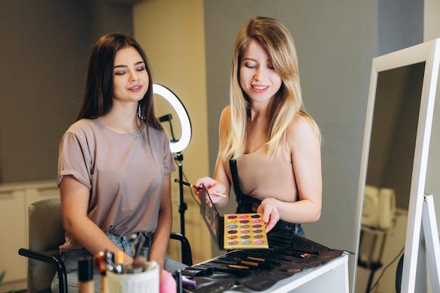 De visagist stelt voor om een keuze te maken uit de kleur make-up of oogschaduw. vrouw met bruin haar die oogschaduw bekijkt. een jonge vrouw zit op een stoel bij een visagist en kijkt naar cosmetica.