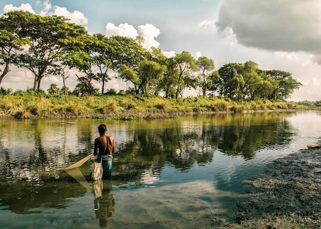 De visser in een kleine dorpsrivier